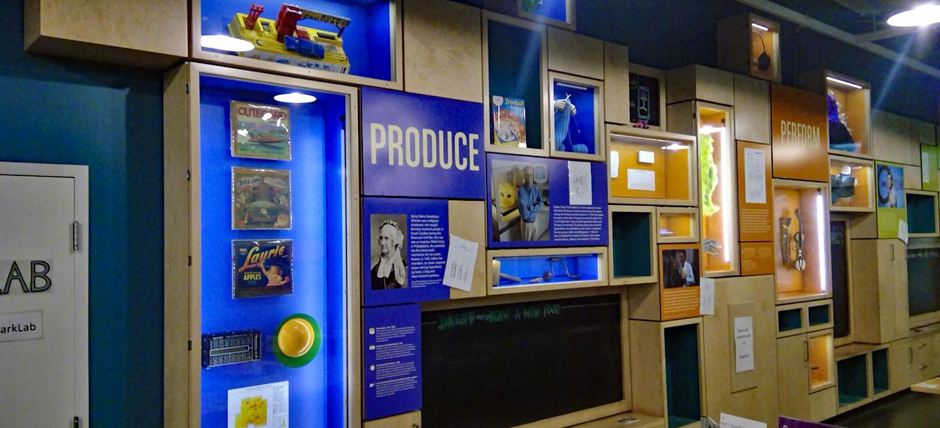 A wall of SparkLab displaying artifacts, props, and text for Produce, Protect, and Perform themes.