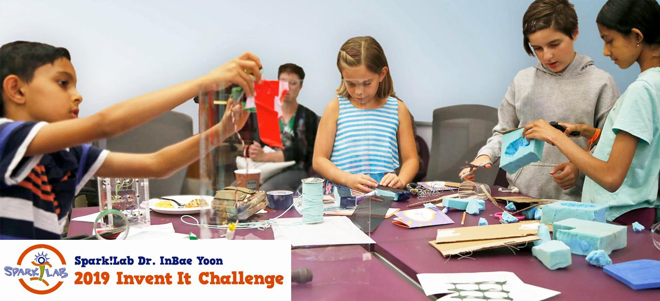 A young boy at left, a young girl in the center, and two pre-teen girls working together at right are at a table covered with craft materials. Each child is focused on his or her creative work.