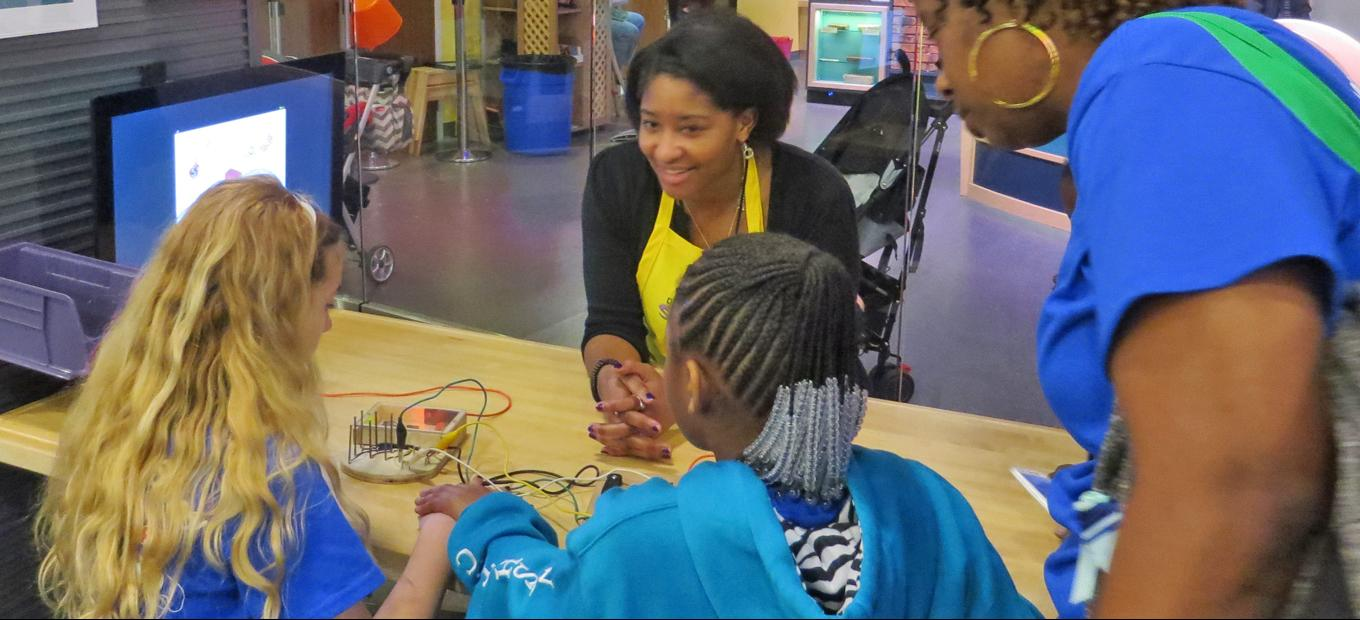 SparkLab volunteer assists two young girls with the Electronic Symphony activity