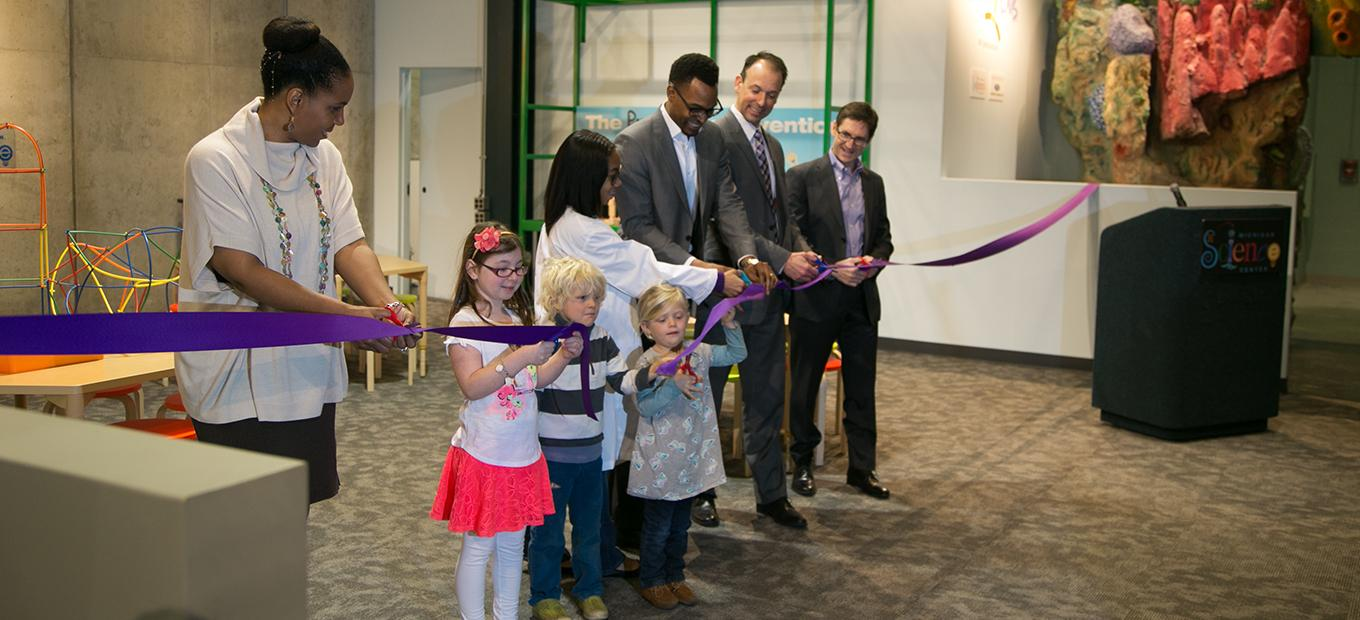 Smithsonian, Ford, and Michigan Science Center officials cut the ribbon to the newest Spark!Lab with the help of a few young visitors