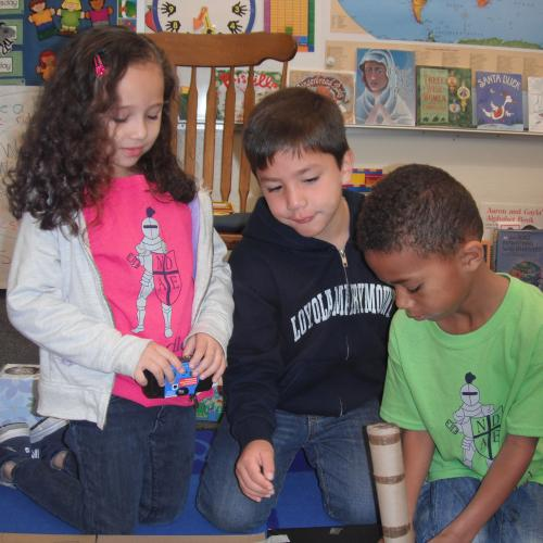 A group of kindergarteners prototype an invention with recyclables