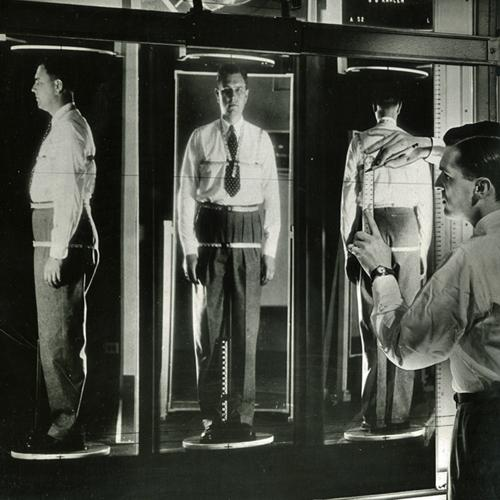 A projection of 3 views of a male customer's reflection in mirrors, from the side, front, and back. He is wearing a tape measure harness that goes around his neck, arm (at the shoulder), chest, waist, and hips.