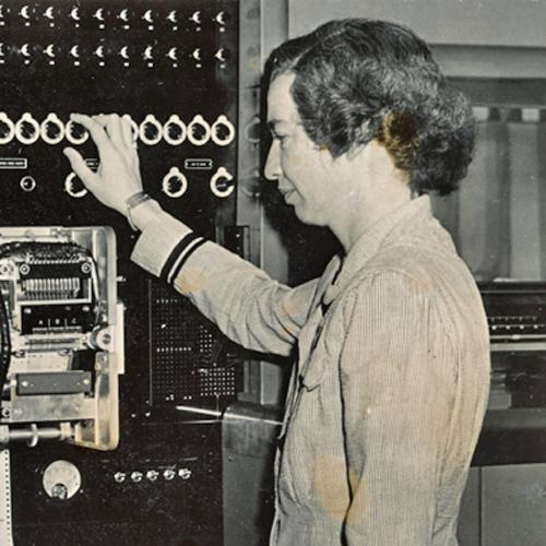 Grace Hopper, wearing her navy uniform, standing in profile to the camera. She has her right hand on one of the many dials that run across the top of the Mark I computer. She is looking at a section of the computer with many gears to move the punched tape code through the machine.