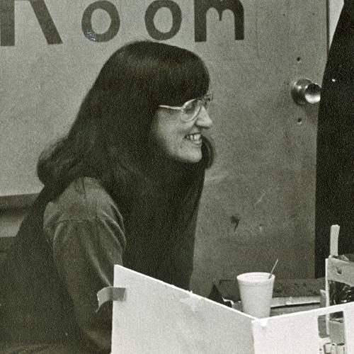 Detail of a photo of Elaine Ostroff, on left, with two other women, looking at a model of a play space. The words Play Room are on the door behind Ostroff.