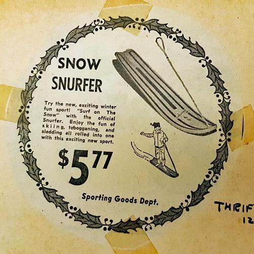 "Newsprint ad for the ""Snow Surfer,"" retailing at $5.77. Text reads, in part, ""Enjy the fun of skiing, tobogganing, and sledding all rolled into one with this exciting new sport."""