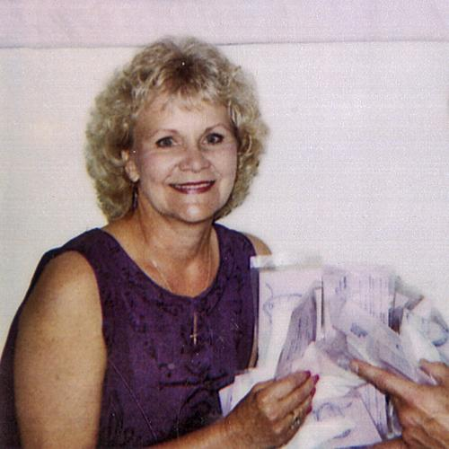 Sharon Rogone, smiling at the camera. She is holding an assortment of unidentified papers. She has curly blonde hair and is wearing a sleeveless navt blue dress. This image has been cropped from a larger photo depicting her and her business partner Kenneth Croteau.