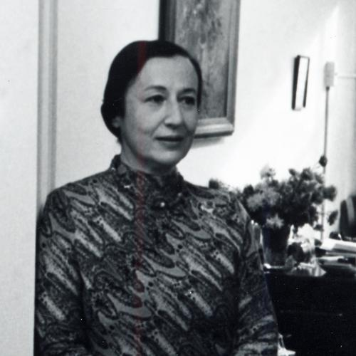 Charlotte Cramer Sachs stands in an interior doorway. A vase of flowers and paintings on the wall are visible over her left shoulder. Her hair is pulled back tightly into a bun and she wears an abstract print dress comprised of wavy diagonal lines. The photo is black-and-white.