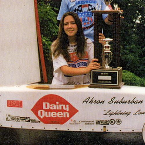Detail of a photo of 14-year-old Laura Shepherd kneels behind her soapbox derby car, holding her trophy, which is resting on the car.