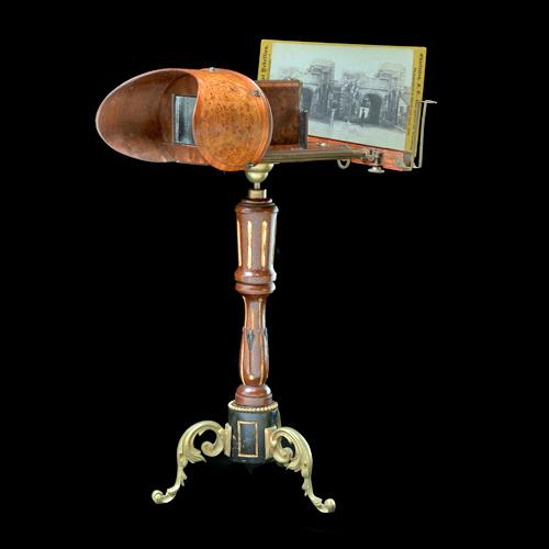 Three-quarters profile view of a free-standing stereoscope. It has curved ornamental metal legs and a carved upright support. A stereograph is in place in the holder.