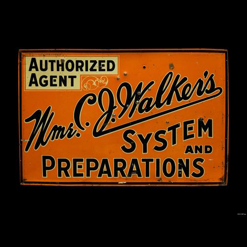 """An orange metal sign with black lettering, reading """"Authorized Agent (highlighted in yellow). Mme. C. J. Walker's System and Preparations."""" Mme. C. J. Walker's is written in cursive across the diagonal of the sign, from lower left to upper right. The other words are written in block letters."""