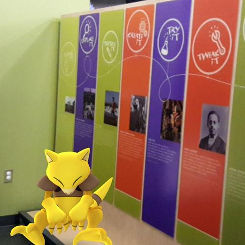 Abra, a Psychic-type Pokémon, sitting near the entrance to Spark!Lab