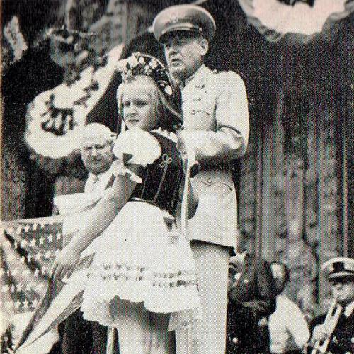 A young girl in traditional Hungarian dress looks at the camera over her shoulder while Charles Eisler at a podium introduces General Herbert Hargreaves during Eisler ambulance donation ceremony, Newark, New Jersey, 1943