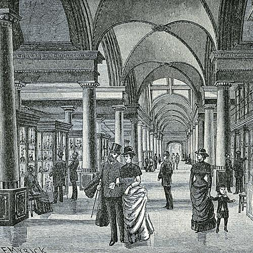 An engraving of the South Hall, Museum of Models, in the US Patent Office, 1887. Several well-dressed men and women and a young child admire the models in glass cases along the walls of a long room with high vaulted ceilings.