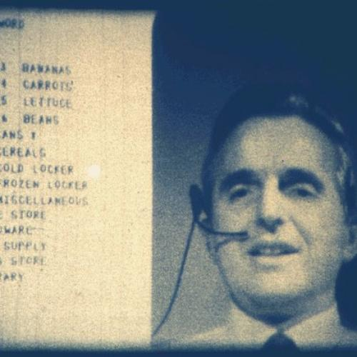 Screenshot of Douglas Engelbart presenting the mother of all demos on 9 December 1968. Engelbart wears a headset and his head and shoulders appear on the right side of the screen. Part of a shopping list, including grocery items bananas, carrots, lettuce, beans, and more, is on the left side.
