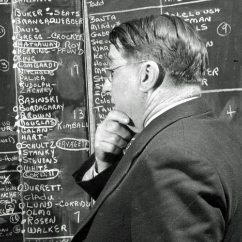 Branch Rickey holding his chin and looking at a blackboard with lists of players' names