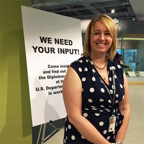 Woman staff member from the US Diplomacy Center stands next to a sign that reads: We need your input!