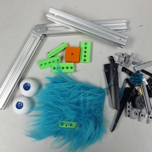 An array of parts from which a creature can be made; includes blue polyester fur, hinged aluminum rods, miscellaneous Lego bits and 3D-printed parts, and small balls made into eyes.