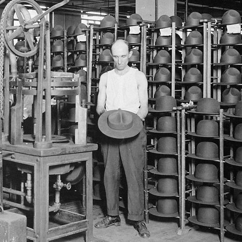 Worker standing next to a machine in the Stetson hat factory in Philadelphia, holding a hat and surrounded by racks of hats, around 1917
