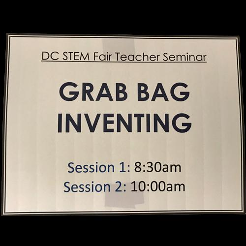 A sign reads CD STEM Fair Teacher Seminar, Grab Bag Inventing, Session 1: 8:30am, Session 2: 10:00am. Black letters on white background.