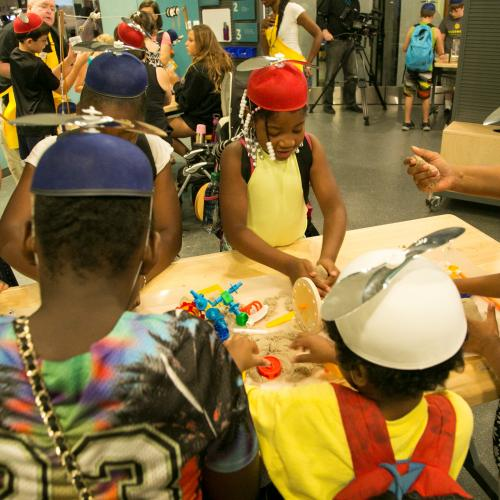A group of children participate in a Spark!Lab activity on opening day