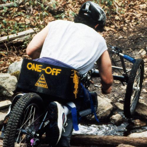 Rear view of a cyclist traveling downhill on Augspurger's handcycle
