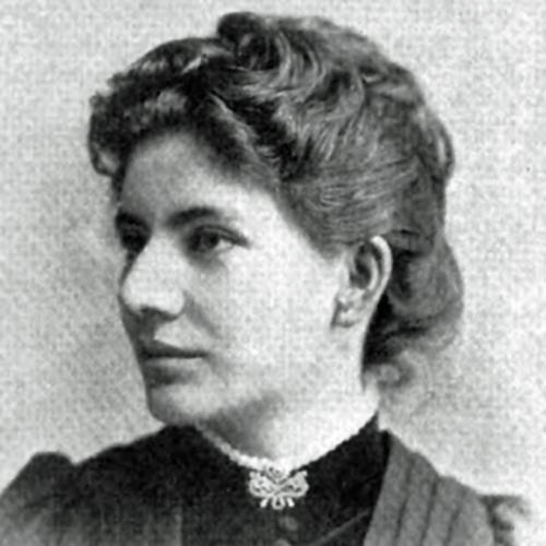 A three-quarters profile head-and-shoulders halftone of architect Sophia Hayden, 1892. She has her hair up in loose waves and wears a high-collared dress, with buttons to the neckline and V-shaped pleats from the shoulders, and a brooch at her throat.