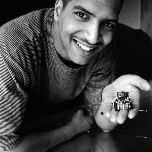 A young Black man holding a tiny robot on his palm