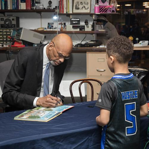 Kareem Abdul-Jabbar signing his book for a young boy