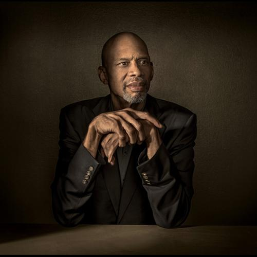 Kareem Abdul-Jabbar sitting at a table with the points of his elbows resting on the table and his hands loosely folded under his chin. He gazes off to the right. Dramatic lighting illuminates his face and hands; the rest of the image is in shadow.