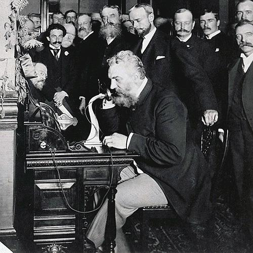Alexander Graham Bell seated at table, speaking into telephone while a group of men watch.