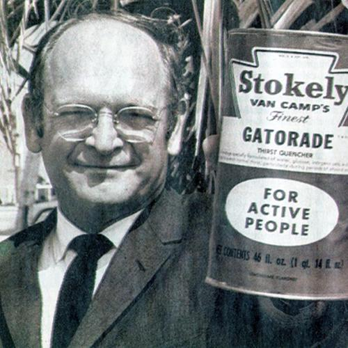 "Black-and-white head-and-shoulders photo of Robert Cade, wearing a jacket and tie. He holds a large can up to the camera. The can is labeled, ""Stokely Van Camp's Finest Gatorade for Active People."""