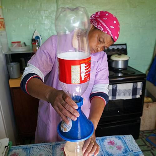 A woman in her kitchen in South Africa pouring water through Folia Water filter, 2016