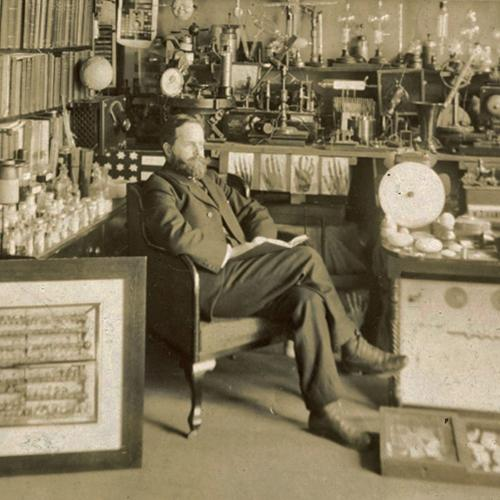 William J. Hammer seated among his large collection of scientific and experimental apparatus