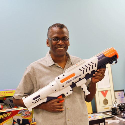 Lonnie Johnson holding a Super Soaker and standing in front of a table covered with his other toy inventions