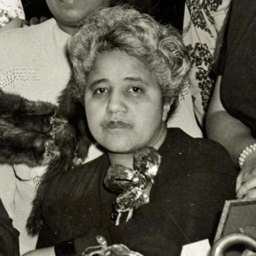 A middle-aged Marjorie Stewart Joyner. The image is cropped from a larger group photo which appears to have been taken at an honorary or celebratory event. Joyner has short, curled hair, is wearing a corsage, and looks straight into the camera. She is not smiling.