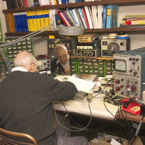 Ralph Baer is sitting at his desk, with his back to the camera, working on something. The desk is covered with equipment and parts and books cover the wall in front of him.