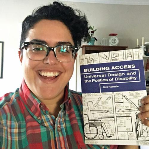 Informal portrait photo of Aimi Hamraie holding her book Building Access.