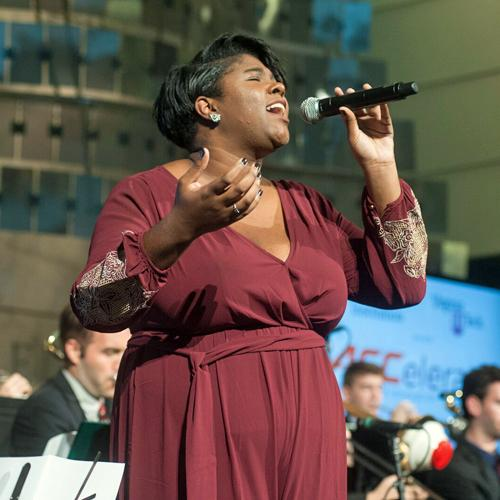 A college-age African American woman is singing into a handheld microphone while a jazz band plays behind her. Her hands are uplifted and her eyes are closed as she performs.