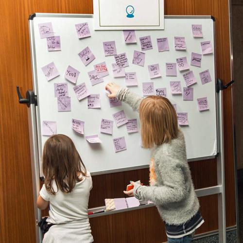 Two young girls place Post-it notes on a whiteboard in response to a sign that reads, Tell us what you think innovation is.