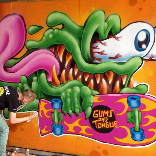 "A graffiti artist is bent over, holding a spray paint can, finishing his colorful artwork that looks like a green slime monster with sharp teeth and bloodshot, bugged-out eyes, with its tongue flapping in the wind. The monster holds a skateboard reading, ""Gums and Tongue."""