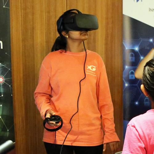 A woman in an orange sweatshirt with the Georgia Aquarium logo is wearing a virtual reality headset and has a small controller in her hand. She is looking up towards the ceiling. From Military Invention Day 2018.