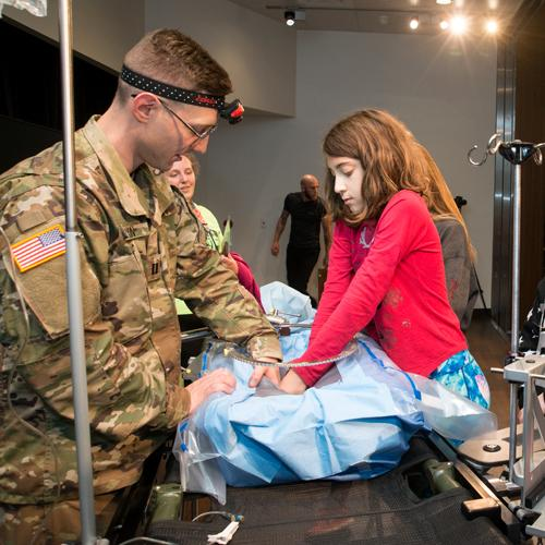 A soldier assists a young girl as she reaches into the body cavity of a dummy patient. The soldier is wearing camouflage fatigues and a headlamp. The dummy patient rests on the SHRAIL system that has been transformed into an operating table. From Military Invention Day 2018.