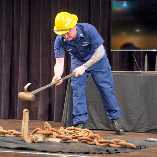 A man wearing blue short-sleeve coveralls and a yellow hard hat swings a tool that is half sledge hammer and half hook at an anchor chain. From Military Invention Day 2018.