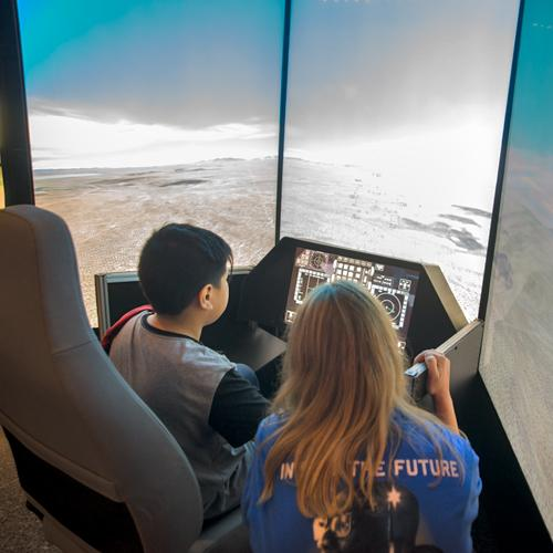 A young boy and girl using a flight simulator
