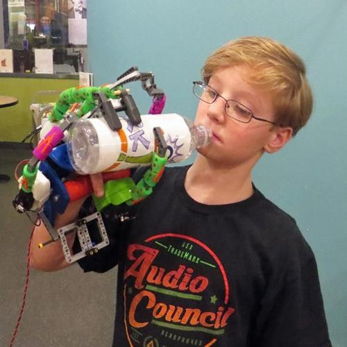 A boy about 11 years old manipulates a robotic hand that he built in SparkLab. He is grasping a bottle with the oversized hand.