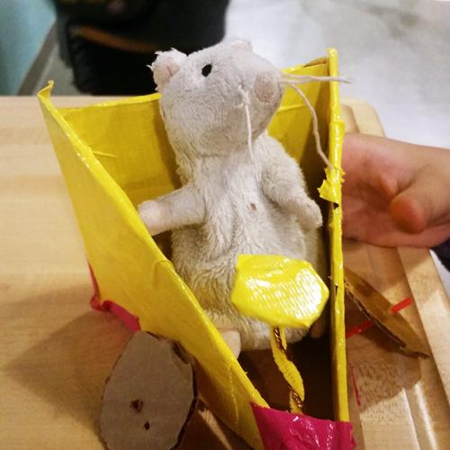 A toy mouse in a yellow, wedge-shaped car