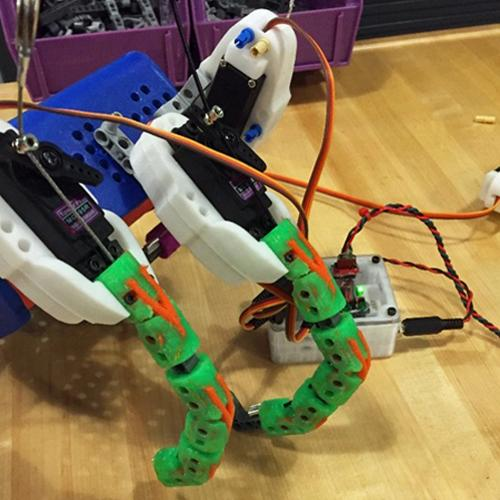 A grouping of different colored #D-printed plastic pieces that form a prosthetic hand with 2 articulated fingers. The fingers are green plastic with orange wishbone-shaped pieces connecting the joints. The hand is connected to an electronic control box.