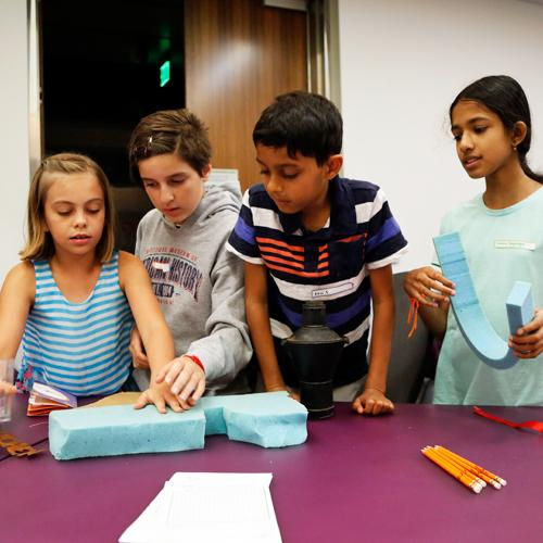 4 kids working together on a hands-on invention activity