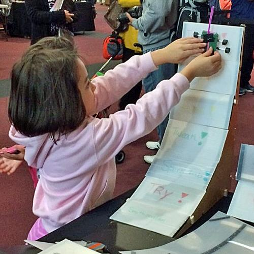 A young girl works on the Invent a Skate Park activity
