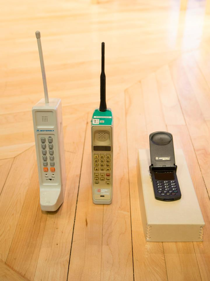 """Two early Motorola """"brick"""" phones and an early flip phone."""